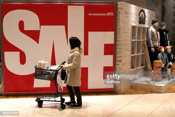 A woman walks past a sales sign at a shopping district in Tokyo Japan January 10 2018