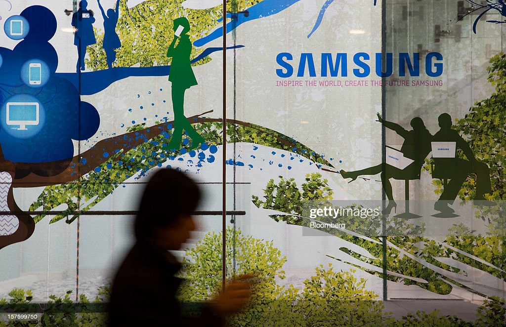 A woman walks past a Samsung Electronics Co. advertisement displayed at the company's Seocho office building in Seoul, South Korea, on Wednesday, Dec. 5, 2012. Samsung Electronics Co. promoted Lee Jae Yong to vice chairman, putting him a step closer to succeeding his father as leader of the world's biggest maker of televisions and mobile phones. Photographer: SeongJoon Cho/Bloomberg via Getty Images