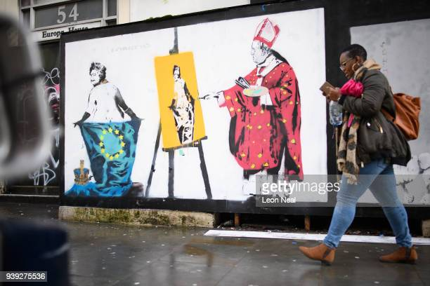 A woman walks past a satirical piece by artist 'Loretto' featuring Queen Elizabeth II being painted while wearing nothing but an EU flag on March 28...