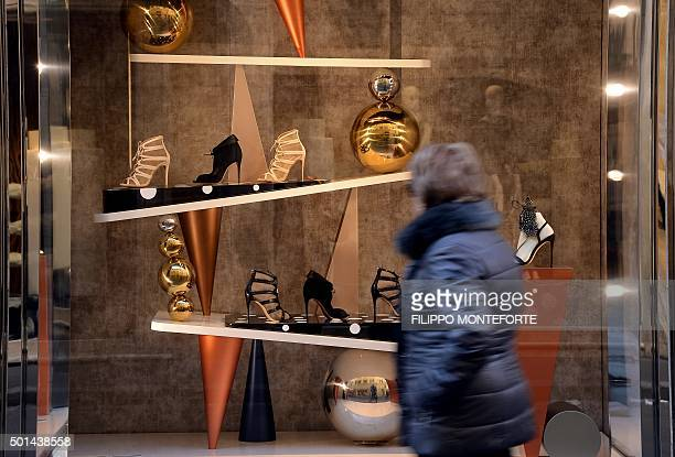 A woman walks past a shoe store reading decorated with Christmas ornaments in downtown Rome on December 15 2015 / AFP / FILIPPO MONTEFORTE