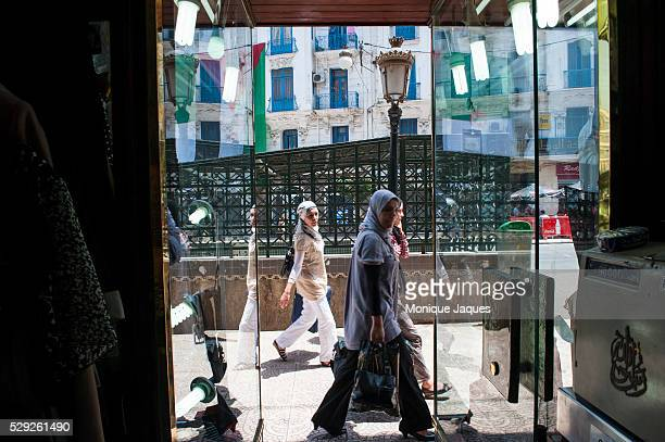 A woman walks past a shop in Downtown Algeirs Algeria
