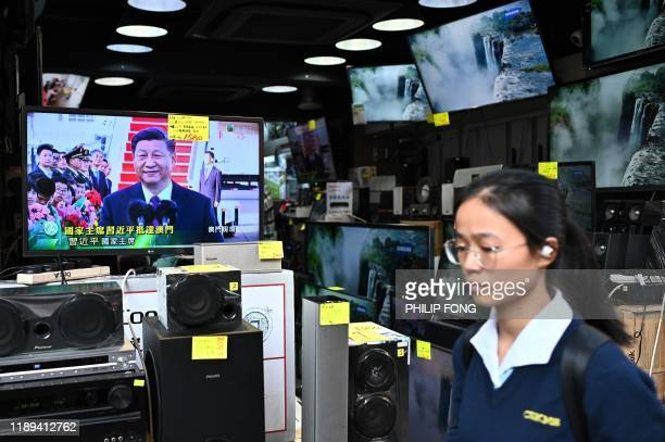 Woman walks past a shop in Sham Shui Po in Hong Kong with a TV showing a live broadcast of Chinese President Xi Jinping's arrival in Macau on...