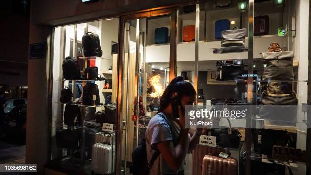 A woman walks past a shop is reflected by a burning garbage during the 5th Anniversary of the murder of Pavlos Fyssas September 2018 marks 5 years...