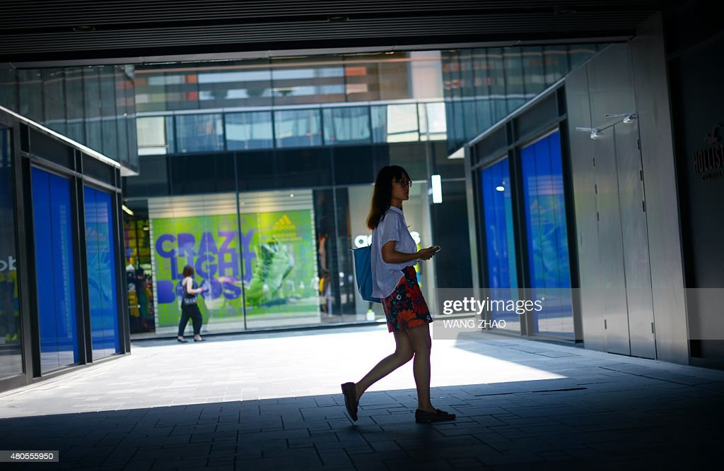 A woman walks past a shopping mall in Beijing on July 13, 2015. China's total trade slumped in the first half of this year, official data showed on July 13, falling well short of the government's targets and dealing a blow to the global economy from its biggest trader in goods.