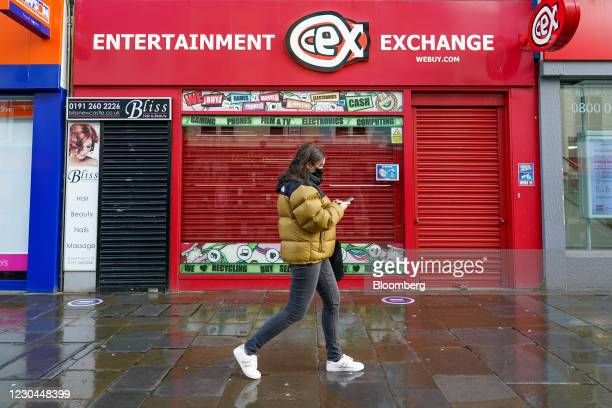 Woman walks past a shuttered cash exchange shop in Newcastle, U.K., on Wednesday, Jan. 6, 2021. U.K. Businesses were suffering even before the latest...