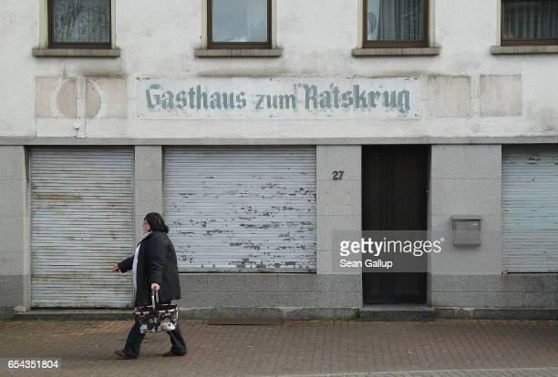 A woman walks past a shuttered pub in Wallerfangen district on March 15 2017 in Saarlouis Germany Saarlouis is in the industrial heartland of...