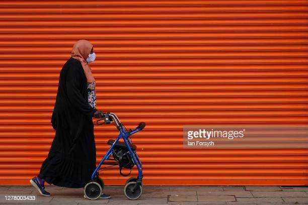 Woman walks past a shuttered shop front in Middlesbrough following criticism of lockdown measures by the Middlesbrough mayor Andy Preston on October...