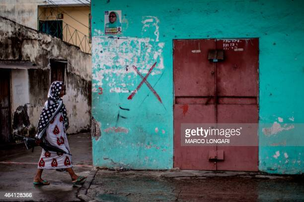 A woman walks past a shuttered shop in the capital Moroni on Grande Comore island on February 22 2015 which has been marked with a red cross...