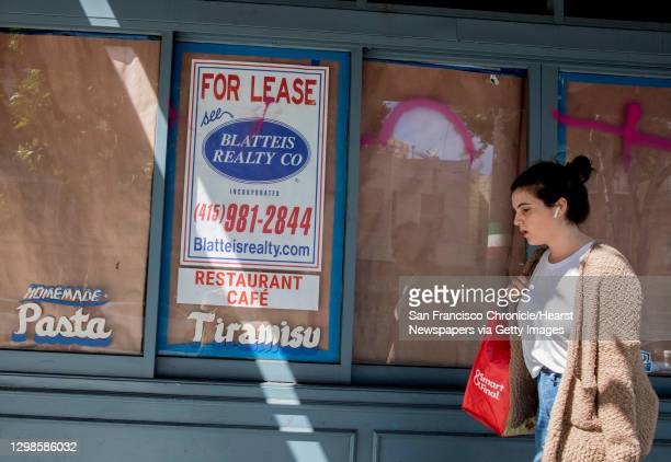 Woman walks past a shuttered storefront along Columbus Avenue in the North Beach neighborhood of San Francisco, Calif. Friday, May 31, 2019.