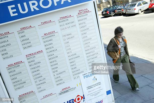 Woman walks past a sign advertising a bus company's destinations in western Europe April 13, 2004 near the main bus station in Cracow, Poland. A...