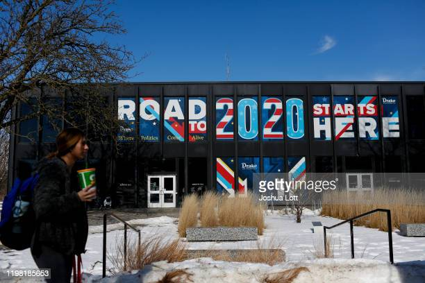 "Woman walks past a sign displayed on a building a Drake University that reads ""Road To 2020 Starts Here"" on February 2, 2020 in Des Moines, Iowa...."