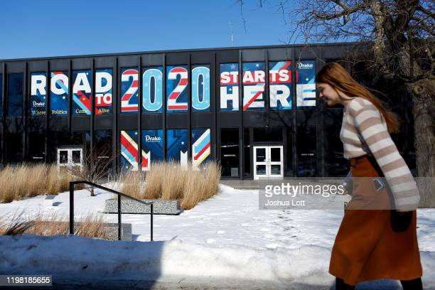 A woman walks past a sign displayed on a building a Drake University that reads Road To 2020 Starts Here on February 2 2020 in Des Moines Iowa...
