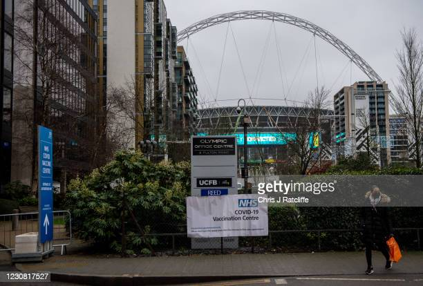 Woman walks past a sign for a Covid-19 vaccination centre near Wembley Stadium on January 27, 2021 in London, United Kingdom. AstraZenecas chief...