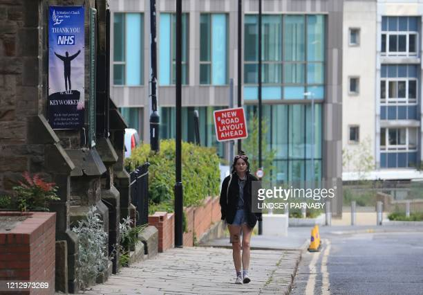 A woman walks past a sign outside a church thanking the workers of Britain's NHS in Sheffield northern England on May 14 following an easing of the...