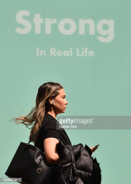 Woman walks past a sign saying 'strong in real life' in Leeds City Centre on May 27, 2021 in Leeds, England.