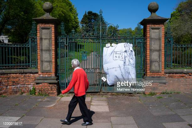 A woman walks past a sign thanking the NHS on the gates of a closed public park on April 19 2020 in Newport United Kingdom The Coronavirus pandemic...