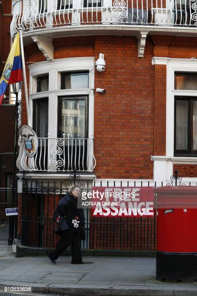 A woman walks past a sign that reads 'free assange' on the facade of the Ecuadorian Embassy in London on January 26 2018 where WikiLeaks founder...