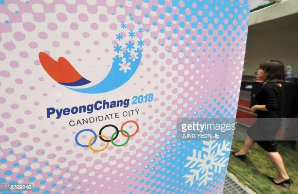 A woman walks past a slogan and logo for Pyeongchang's bid for the 2018 Winter Olympics during a stage rehearsal at the ski jump stadium in the...