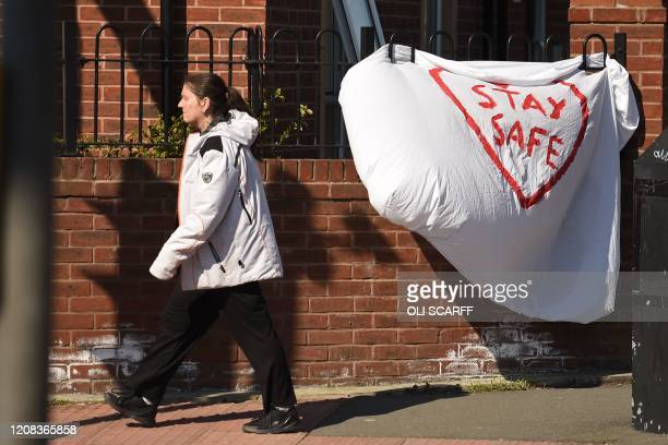 "Woman walks past a slogan asking people to ""stay safe"", written on a bed sheet attached to some railings in Manchester, north-west England, on March..."