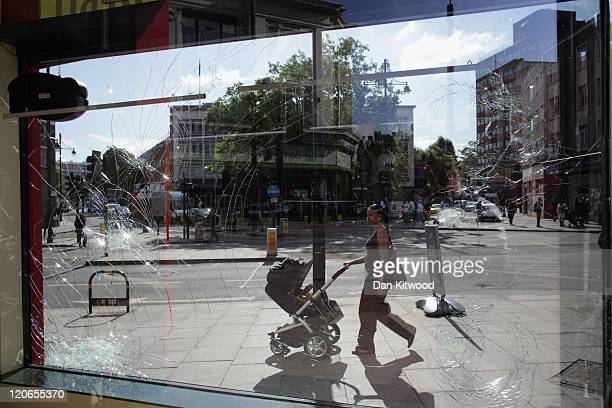 A woman walks past a smashed store front in Brixton on August 8 2011 in London England Widespread rioting and looting took place across many parts of...