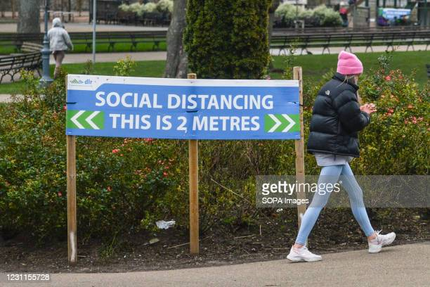 Woman walks past a social distancing sign during the Level 5 Covid-19 restrictions. The Department of Health reported on February 11 a total of 862...