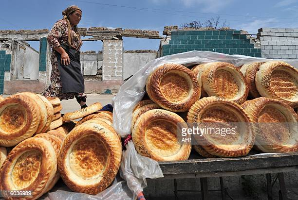 A woman walks past a stall selling cakes in the village of Shark near a town of Osh some 750 km from Bishkek on June 11 2011 Kyrgyzstan on Friday...