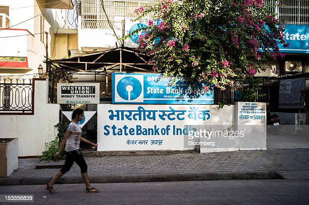 A woman walks past a State Bank of India branch in Jaipur Rajasthan India on Wednesday Oct 3 2012 The Indian economy will expand 56 percent in the...