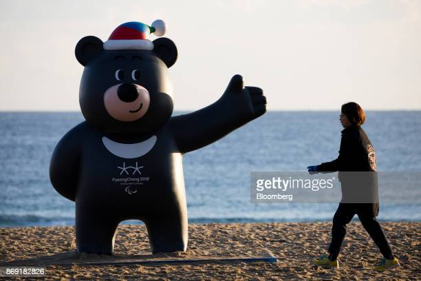 A woman walks past a statue of the 2018 PyeongChang Winter Olympic Games mascot Bandabi at Gyeongpo beach near the Gangneung Ice Arena one of the...