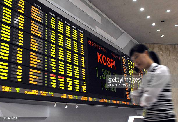 A woman walks past a stock index board at the Korea Exchange in Seoul on October 6 2008 South Korean shares closed 43 percent lower October 6 on...