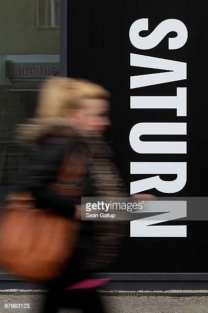 A woman walks past a store of German consumer electronics retail chain Saturn on March 12 2010 in Berlin Germany Saturn is owned by Metro Group which...