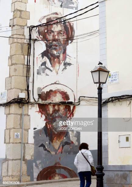 A woman walks past a street art mural on the facade of a house in Fanzara near Castellon de la Plana on December 15 2016 Fanzara a Spanish hamlet in...