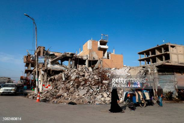 Woman walks past a street vendor and a destroyed building in the Syrian city of Raqa on October 18, 2018. - A year after a US-backed alliance of...