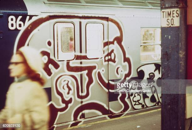 A woman walks past a subway train covered in graffiti in the Times Square subway station New York City New York May 1973 Image courtesy National...