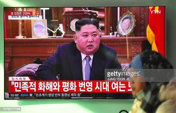 A woman walks past a television news screen showing a New Year speech by North Korean leader Kim Jong Un at a railway station in Seoul on January 1...