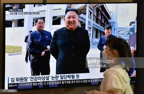 Woman walks past a television news screen showing a picture of North Korean leader Kim Jong Un attending a ceremony to mark the completion of Sunchon...