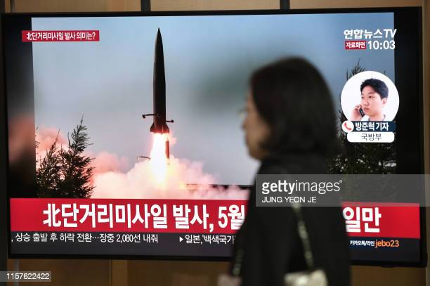 Woman walks past a television news screen showing file footage of a North Korean missile launch, at a railway station in Seoul on July 25, 2019. -...