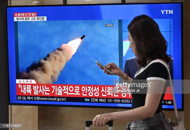 TOPSHOT A woman walks past a television news screen showing file footage of a North Korean missile launch at a railway station in Seoul on September...
