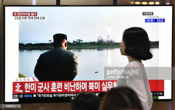 Woman walks past a television news screen showing file footage of North Korean leader Kim Jong Un watching a missile launch, at a railway station in...