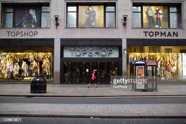 Woman walks past a temporarily-closed branch of clothing retailer Topshop on Oxford Street in London, England, on November 18, 2020. Across England...
