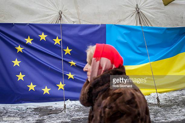 A woman walks past a tent displaying the European Union and Ukrainian flags in Independence Square on January 28 2014 in Kiev Ukraine Ukraine's...