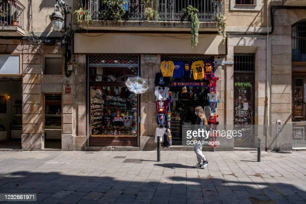 Woman walks past a tourist souvenir shop in front of the Palau de la Musica. There is one week left for the state of alarm decreed by the Spanish...