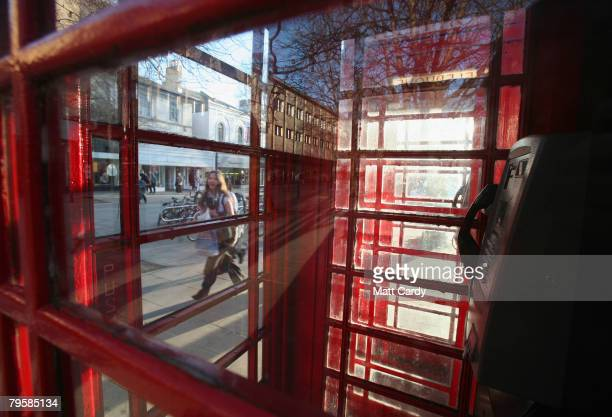 A woman walks past a traditional red telephone box in a street in Cheltenham on February 6 2008 in Gloucestershire England According to BT payphone...