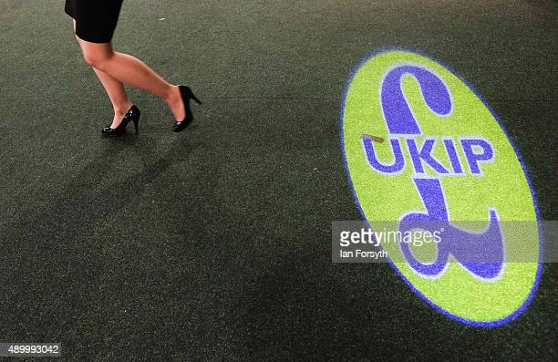 A woman walks past a UK Independence Party logo projected onto a carpet during the UK Independence Party annual conference at Doncaster Racecourse on...