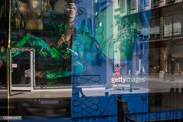 A woman walks past a Versace store on New Bond Street on May 19 2020 in London England As shops gear up to open after a long period of closure...
