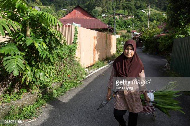 A woman walks past a village in Air Itam that forms part of the 234 acre land acquired by the 1MDB fund on August 1 2018 in Penang Malaysia Around...