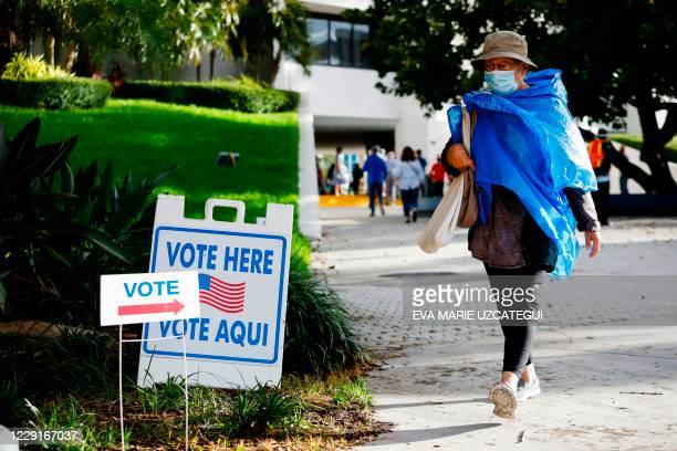 "Woman walks past a ""Vote Here"" sign at Miami Beach City Hall in Miami Beach, Florida on October 19, 2020. - President Donald Trump lashed out at..."