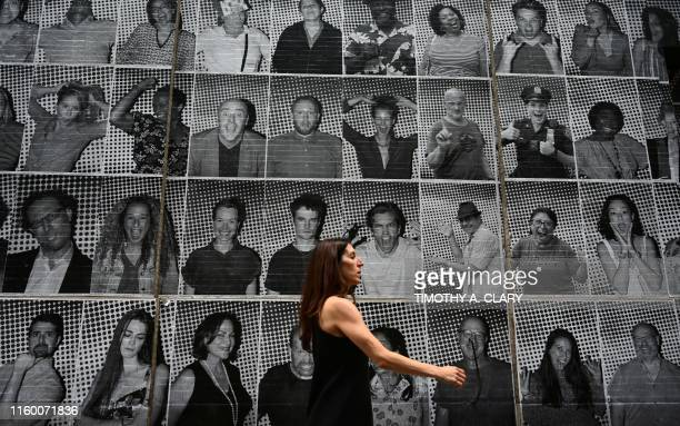 A woman walks past a wall at the back of Broadway's Hudson Theatre with artwork from French photographer and artist JR and his global art project...