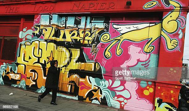 A woman walks past a wall bearing graffiti near the site of the London 2012 Olympics in the East London borough of Stratford on February 24 2006 in...