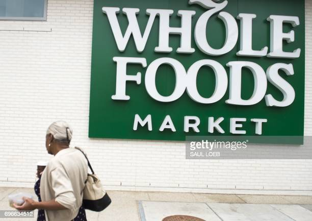A woman walks past a Whole Foods Market in Washington DC June 16 following the announcement that Amazon would purchase the supermarket chain for $137...