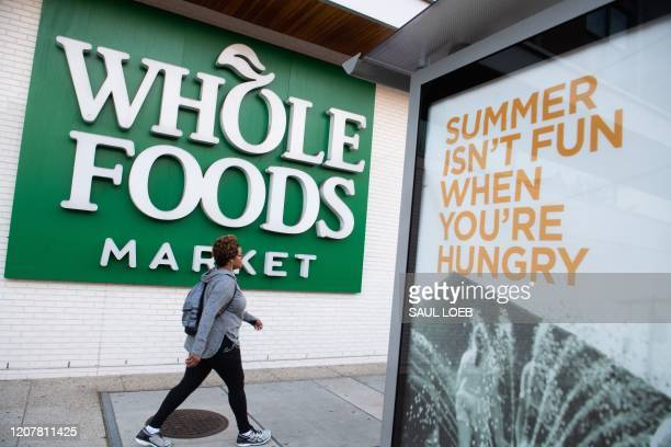 Woman walks past a Whole Foods supermarket in Washington, DC, March 20, 2020. - Whole Foods, like several other retailers, is reserving some hours...